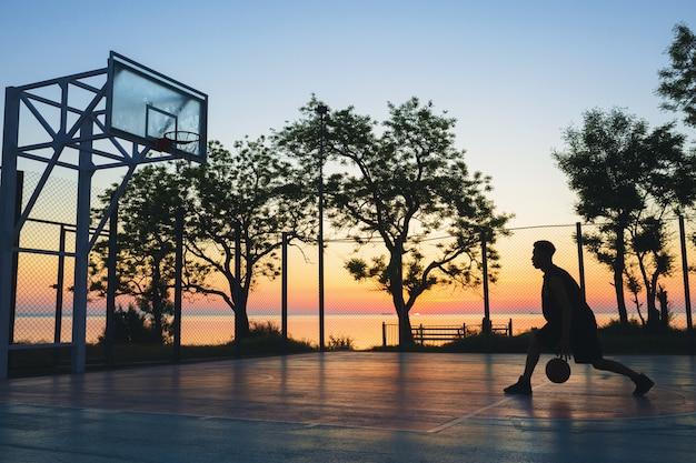 スポーツをして、日の出、シルエットでバスケットボールをしている黒人男性 無料写真