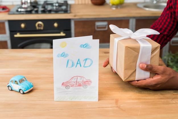 Black man holding gift box near greeting card Free Photo