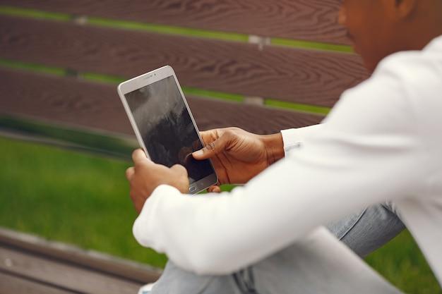 夏の街で白いセーターの黒人男性 無料写真