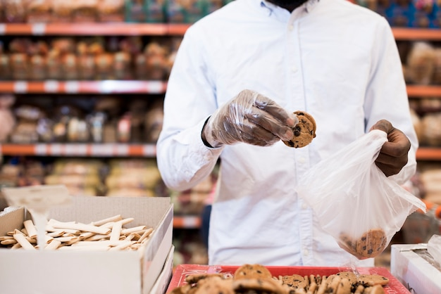 Black man putting cookies in plastic bag in grocery Free Photo