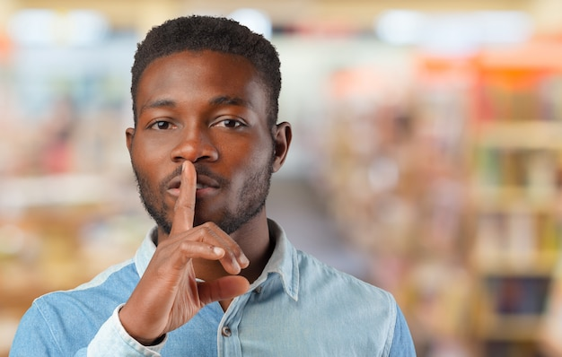 Black man showing silence gesture with finger on his lips Premium Photo