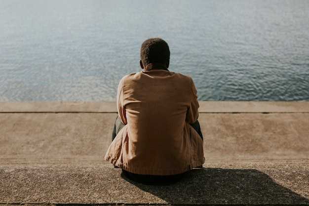 Uomo nero seduto vicino all'acqua Foto Gratuite