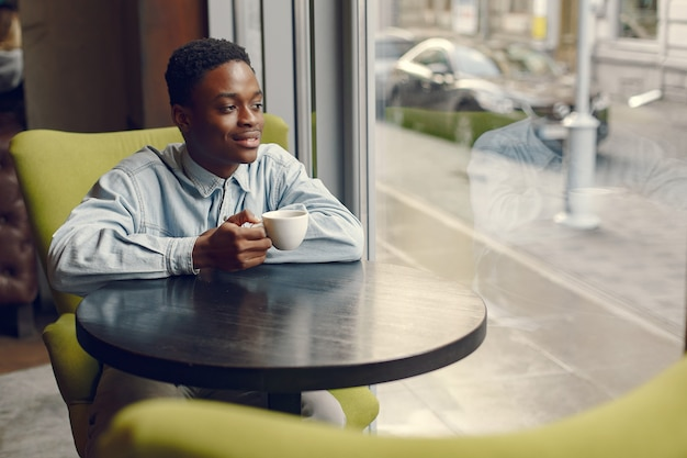 Black man sitting in a cafe and drinking a coffee Free Photo