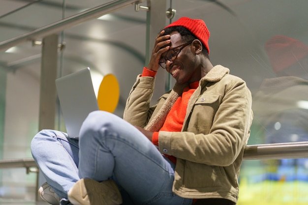 Black man sitting on the floor talking in video chat on laptop chatting in social networks, smiling Premium Photo