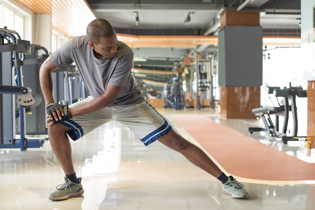 Black man stretching leg in gym Free Photo