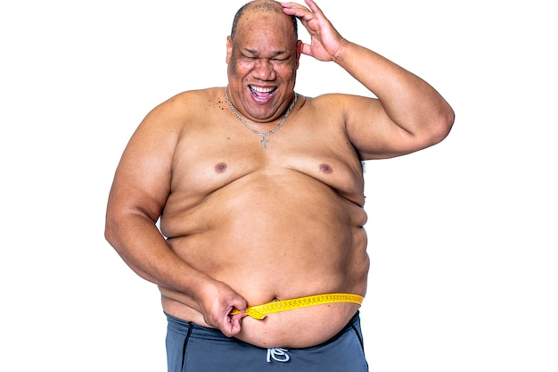 Black man who is obese and on a diet measures his waist with a tape measure happy and smiling for having lost weight Premium Photo