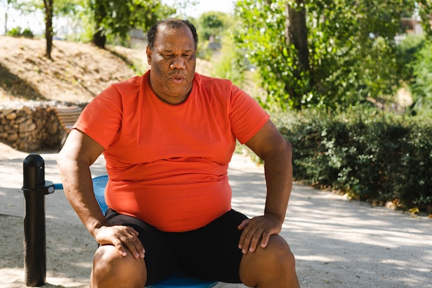 Black man with obesity sitting after exercising to lose weight Premium Photo