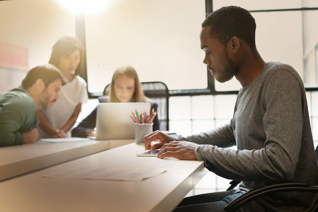 Black man working in modern office space with co workers Premium Photo