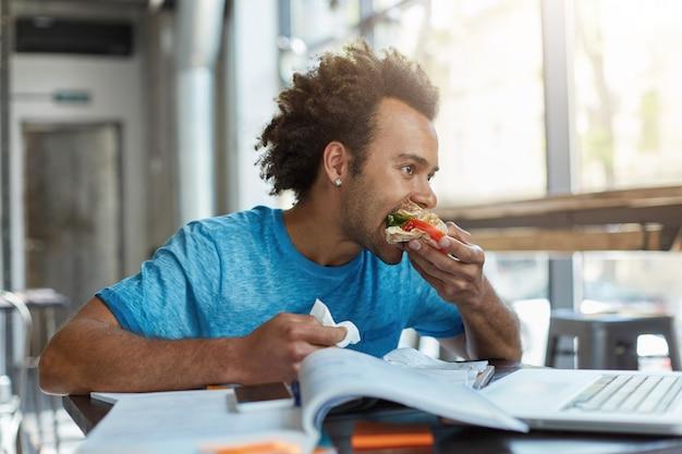黒い混血の男子生徒がサンドイッチを食べるための休憩の勉強で忙しい。 無料写真