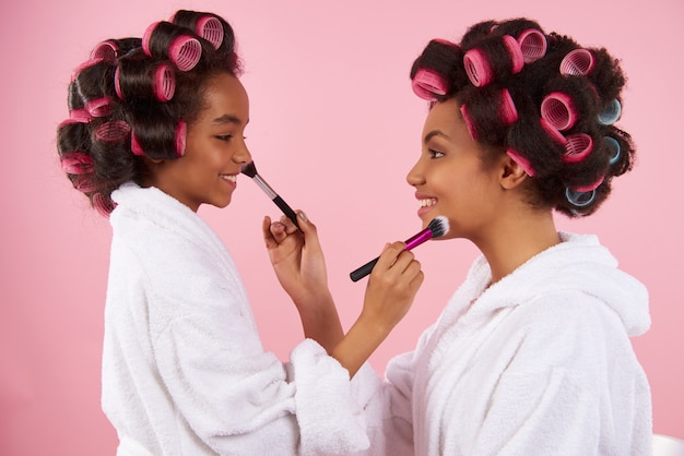 Black mom and girl paint each other. Premium Photo