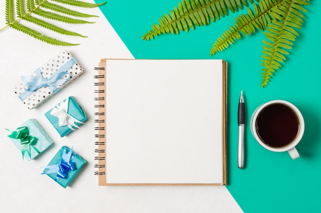 Black notepad; presents with coffee cup arranged on white and turquoise backdrop Free Photo