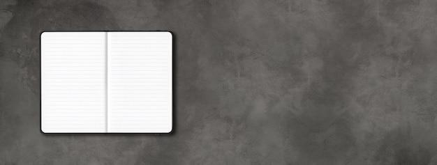 暗いコンクリートの背景に分離された黒いオープンラインのノートブックのモックアップ。横バナー Premium写真