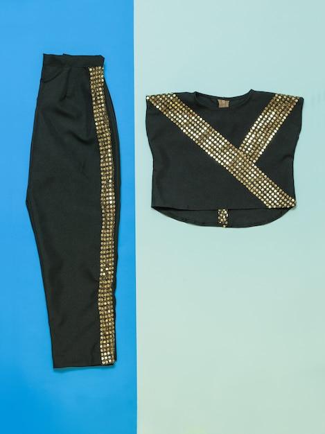 光沢のある仕上がりのブラックパンツとブラウス。ゴールドトリムダンスコスチューム付きブラック Premium写真