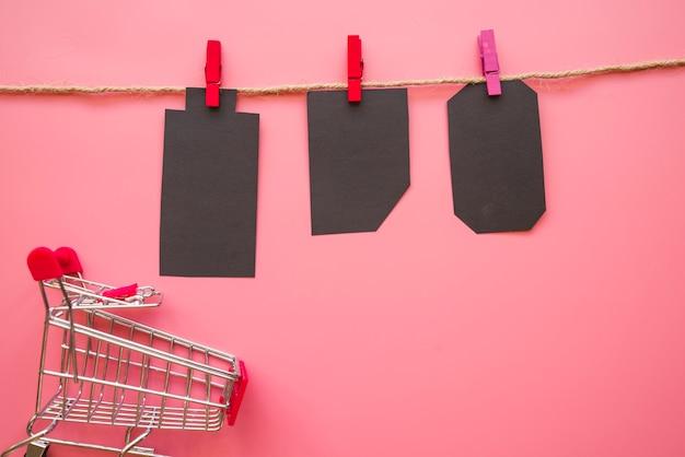 Black paper tallies hanging on thread near shopping trolley Free Photo