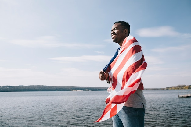 Black patriotic man wrapped in american flag Free Photo
