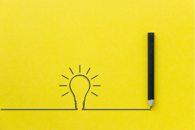 Black pencil on yellow backgroud with light bulb line Premium Photo