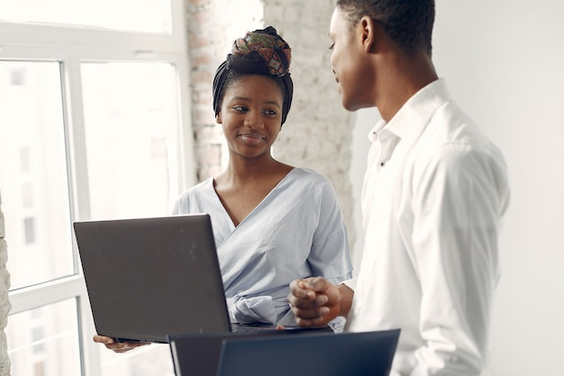 Black people standing on a white wall with a laptop Free Photo