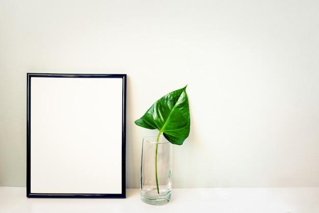Черная рамка для фотографий и зеленое растение в хрустальной вазе, аранжировано против пустой серой стены. Premium Фотографии