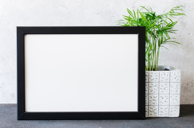 Bingkai foto hitam dan tanaman indah dalam pot beton.  interior kamar bergaya Skandinavia.  Foto Premium
