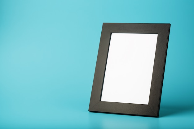 Black photo frame with free space on a blue background. Premium Photo
