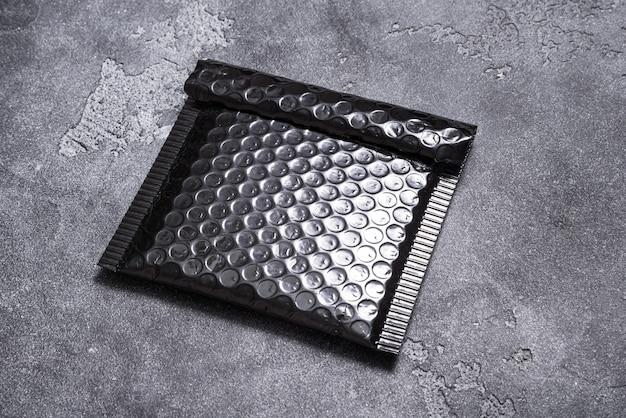 灰色の背景に黒いプラスチックのバブル封筒 Premium写真