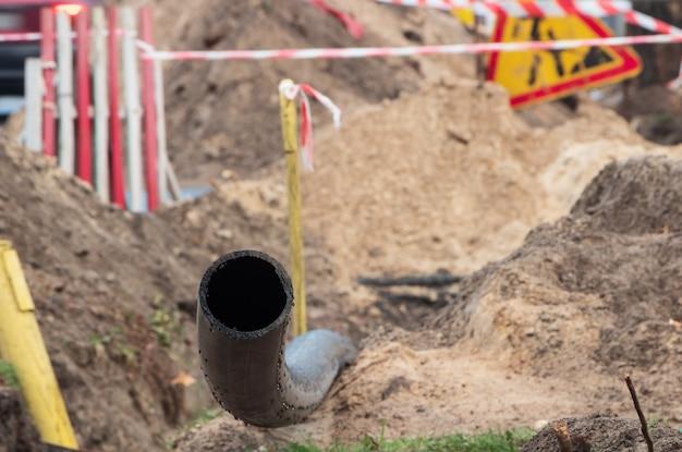 地下水供給用の黒いプラスチックパイプ。塩ビパイプ。下水道システムの修理。閉じる。 Premium写真