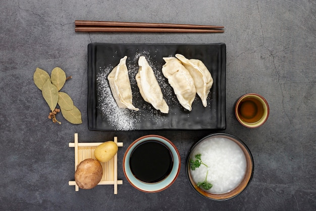 Black plate of dim sum with rice soup bowl on a grey background Free Photo