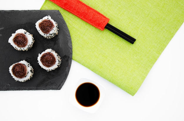 Black plate with sushi rolls on a white background with soy sauce bowl and chopsticks Free Photo