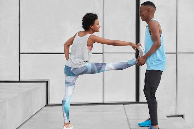黒人のポジティブな男性インストラクターは、女性の研修生が柔軟性のためにエクササイズをしたり、白い壁に向かって階段に立ったり、スポーツウェアを着て幸せな表情をしたりするのを助けます。人、スポーツ、トレーニングの概念 無料写真