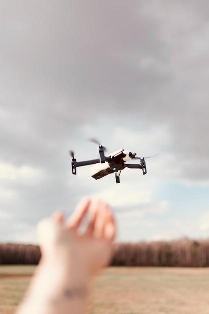 Drone quadricottero nero su un cielo nuvoloso Foto Gratuite