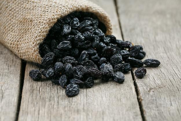 Black raisins in burlap bag over wooden gray table Premium Photo