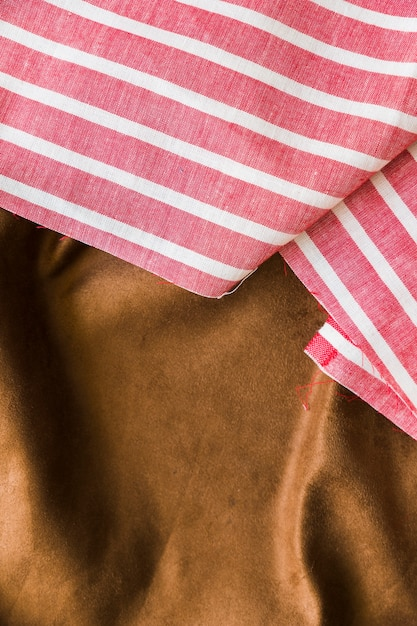 Black and red striped pattern fabric over the smooth brown textile Free Photo