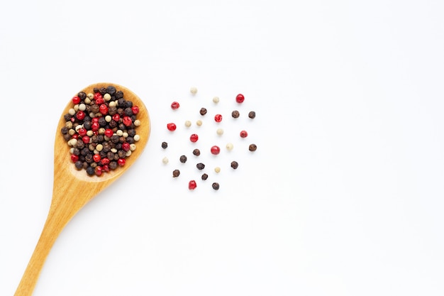 Black, red and white peppercorns on white Premium Photo
