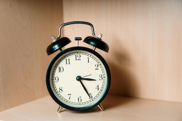 Black retro alarm clock stands on a light wooden shelf. classic alarm clock. Premium Photo