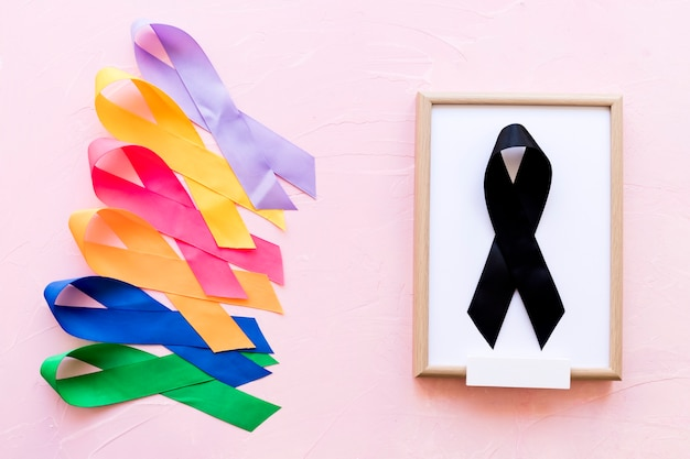 Black ribbon on white wooden frame near the row of colorful awareness ribbon Free Photo