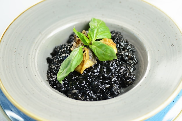 Black rice risotto with fish and basil Premium Photo