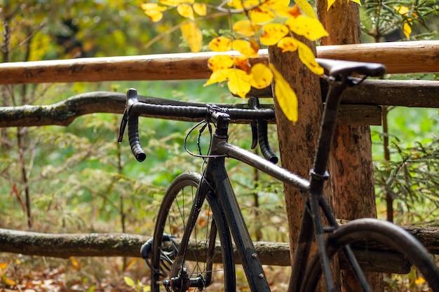 Черный дорожный велосипед припаркован возле старого деревянного забора в осеннем парке. дождливая пасмурная погода Premium Фотографии