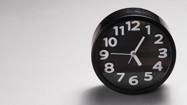 Black round alarm clock on gray background Free Photo