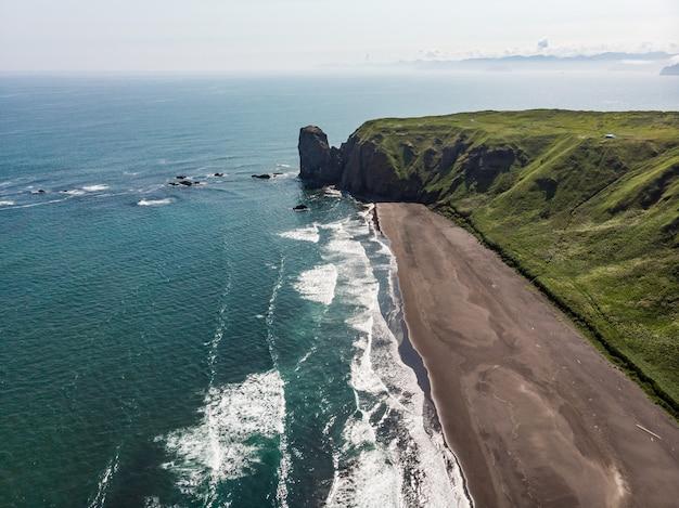 Пляж рейнисфьяра с черным песком и гора рейнисфьял с мыса дирхолай на южном побережье исландии. Premium Фотографии