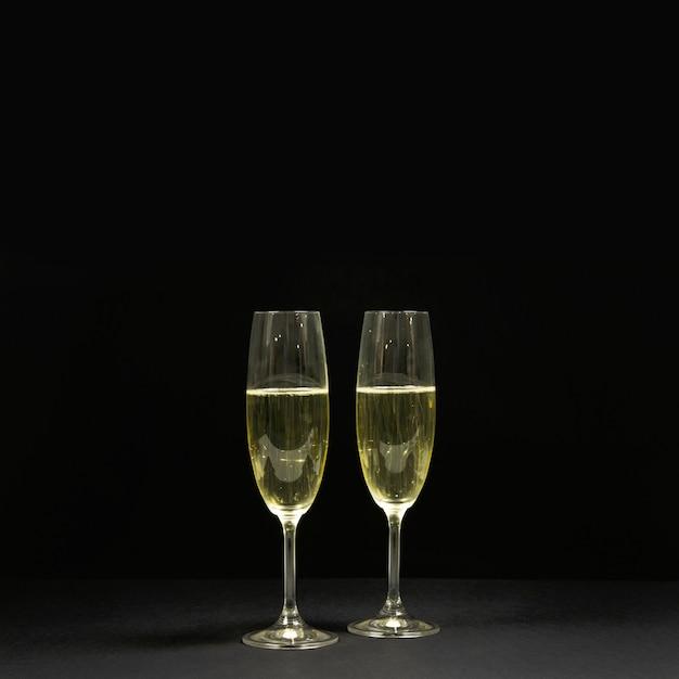 Черная сцена с двумя бокалами шампанского. Бесплатные Фотографии