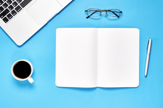 Black screen notebook blank and laptop placed blue background. Premium Photo