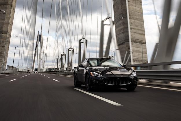 다리 도로에서 운전하는 검은 세 단 자동차. 무료 사진