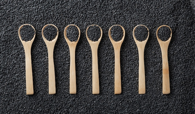 Black sesame seeds in wooden spoons on a background of scattered sesame seeds Premium Photo