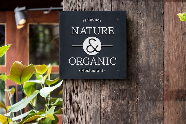 Black signage on a rustic wooden wall mockup Premium Photo