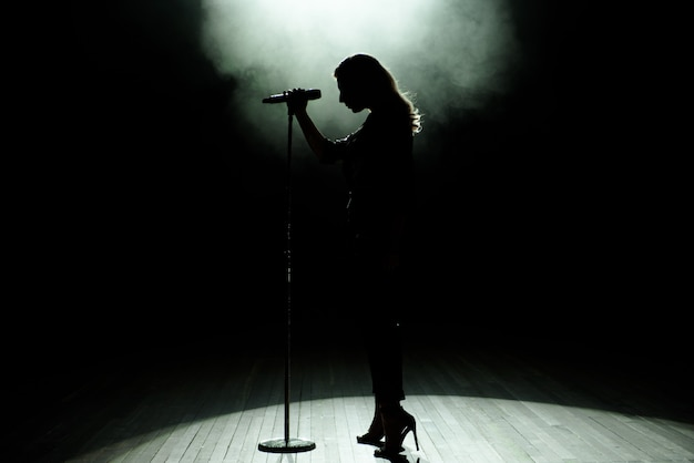 Black silhouette of female singer with white spotlights in the background Premium Photo