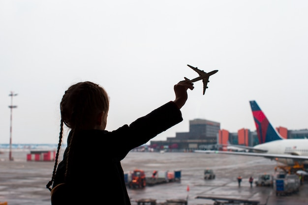 Black silhouette of a small airplane model toy on airport in kids hands Premium Photo