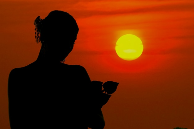 The black silhouette woman standing hugging a lotus flower at sunset Premium Photo