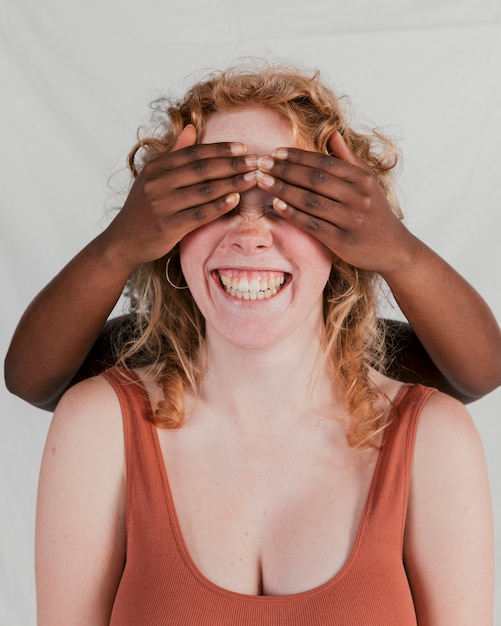 Black skinned woman's hand covering the eyes of her fair friend against grey backdrop Free Photo