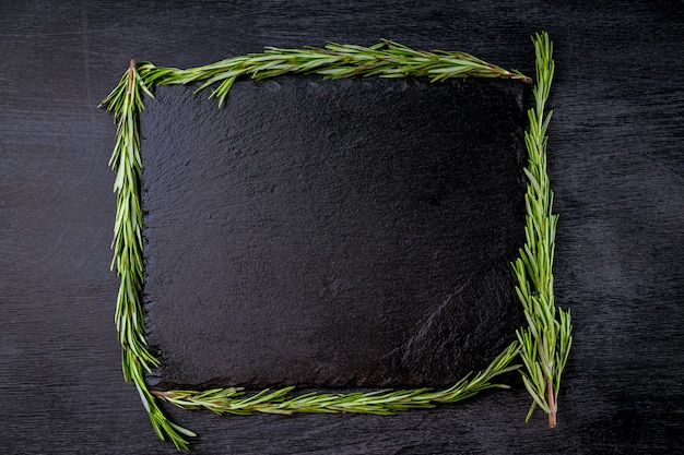Черная грифельная доска и розмарин - пробел для текста. Premium Фотографии