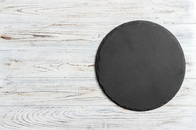 Black slate round stone on wooden background, top view, copy space Premium Photo